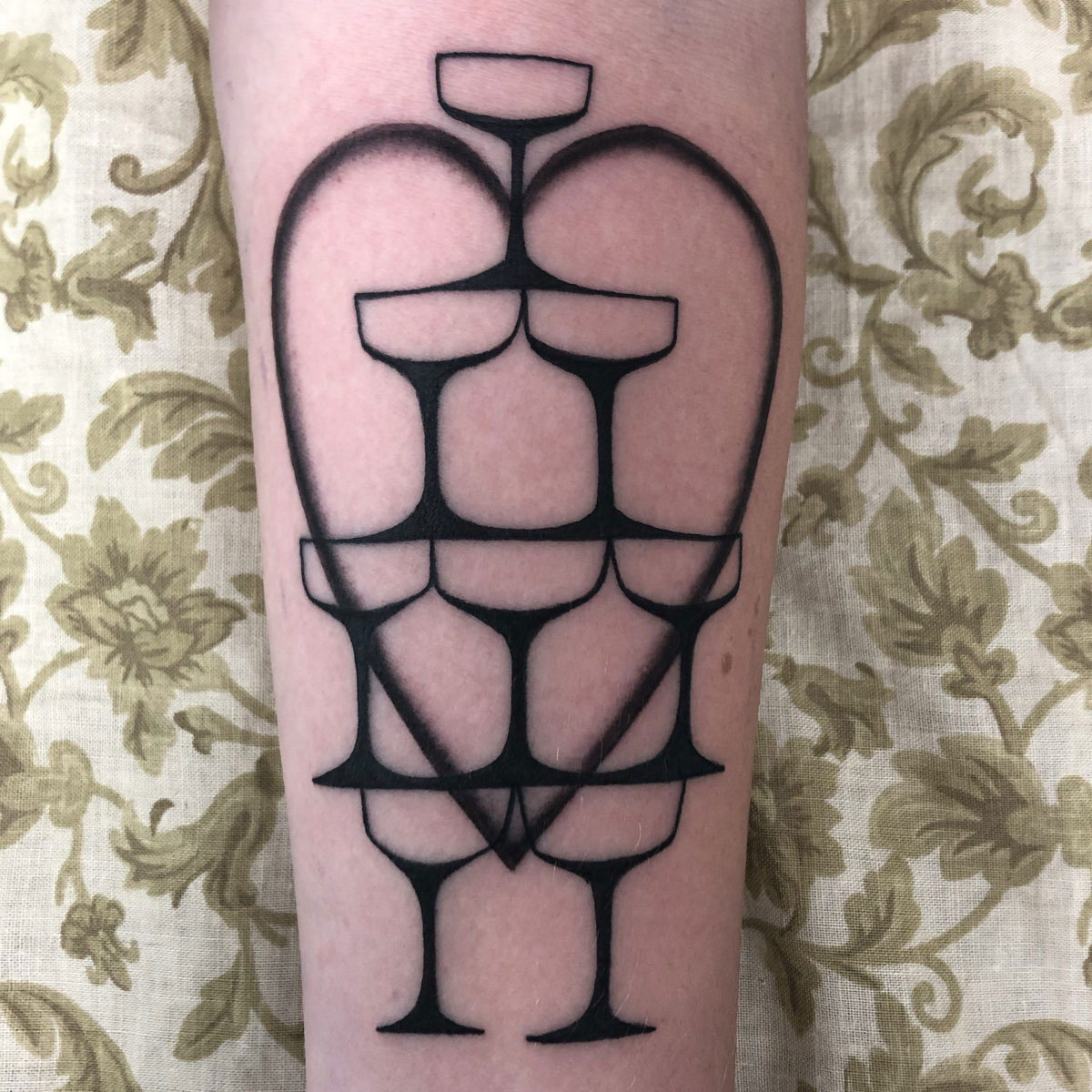 tattoo of a stack of wine glasses pouring into each other forming a heart