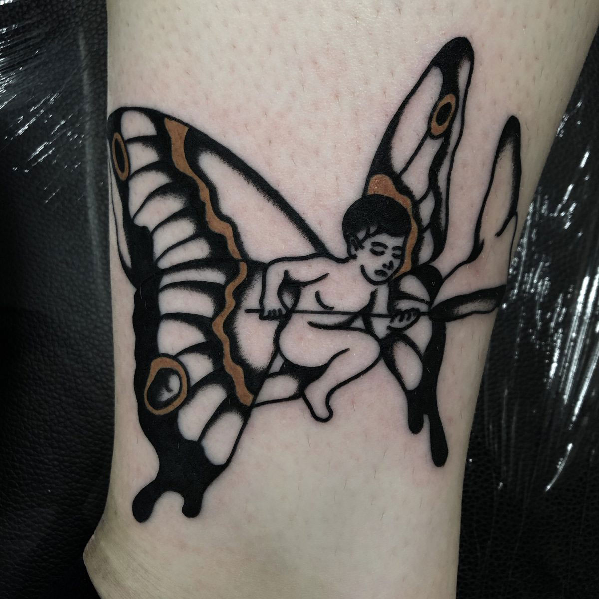 tattoo of a baby cherub with huge butterfly wings