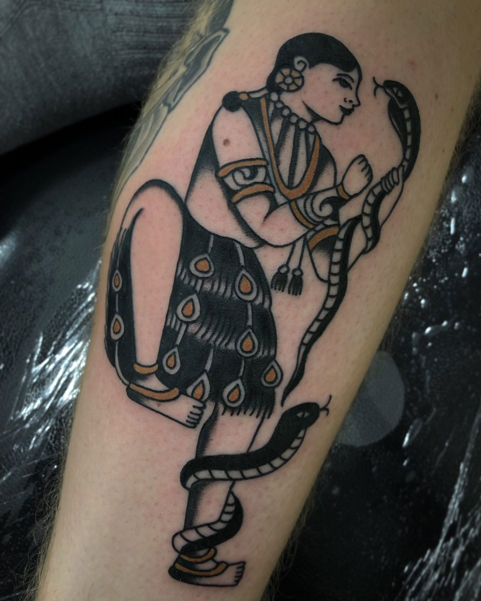 tattoo of snake charmer with two snakes done in european traditional design using black and gold