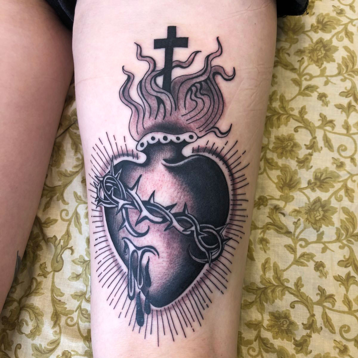 classic black and grey sacred heart tattoo with rays and barbed wire and flames
