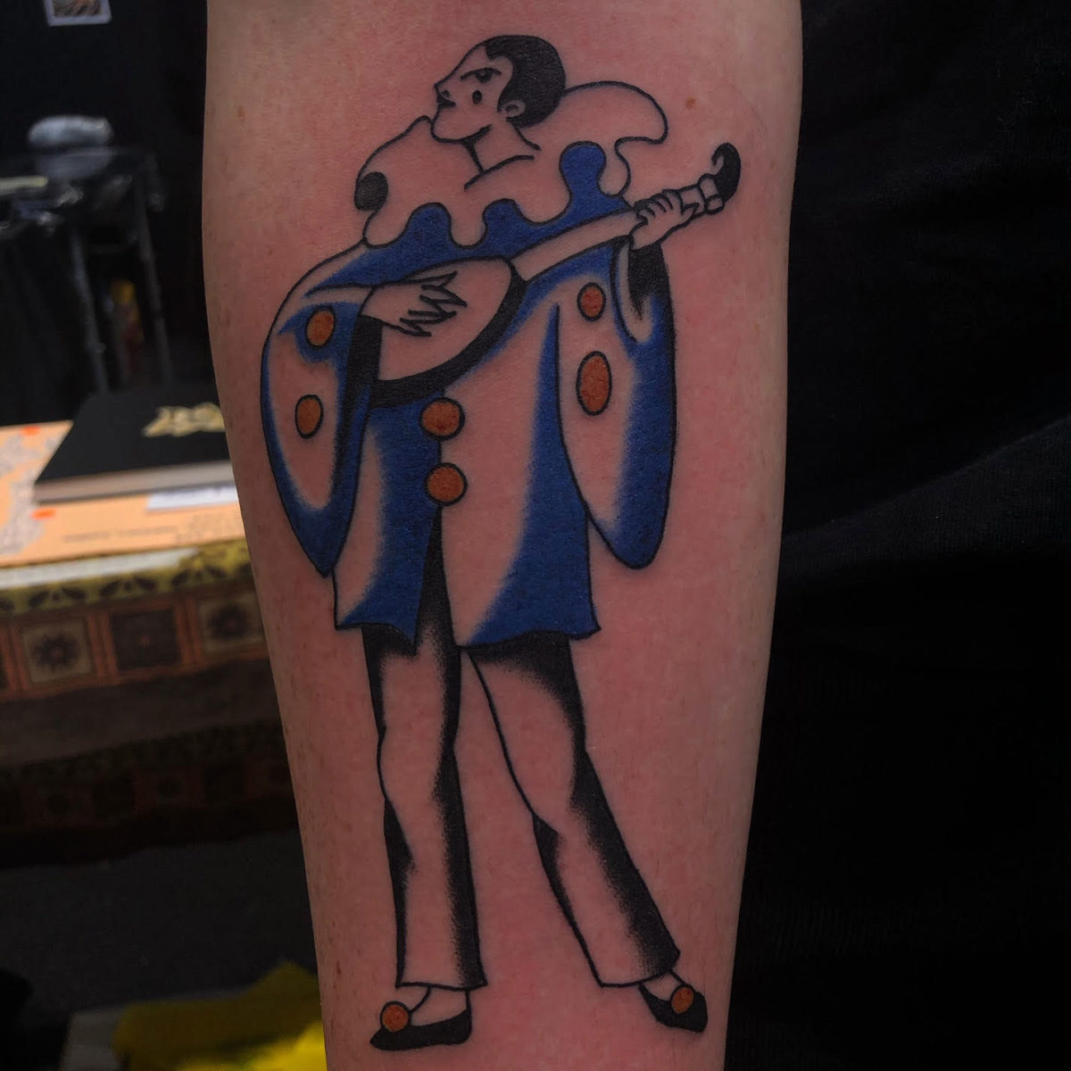 european traditional court jester tattoo musical instrument tattooed with black blue and gold on forearm