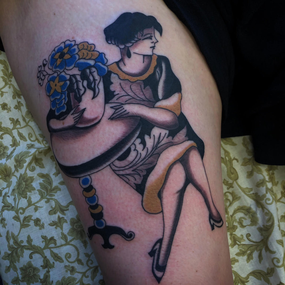 tattoo of victorian lady sitting at table holding a pot full of plants wearing ornamental dress