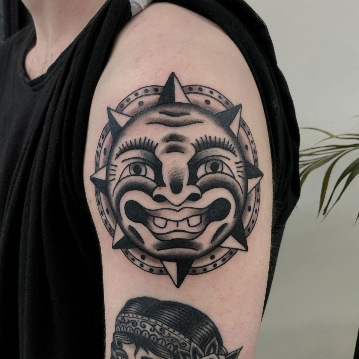 Traditional blackwork tattoo of a sun with a face inspired by bert grimm tattooed on the upper arm in black and grey