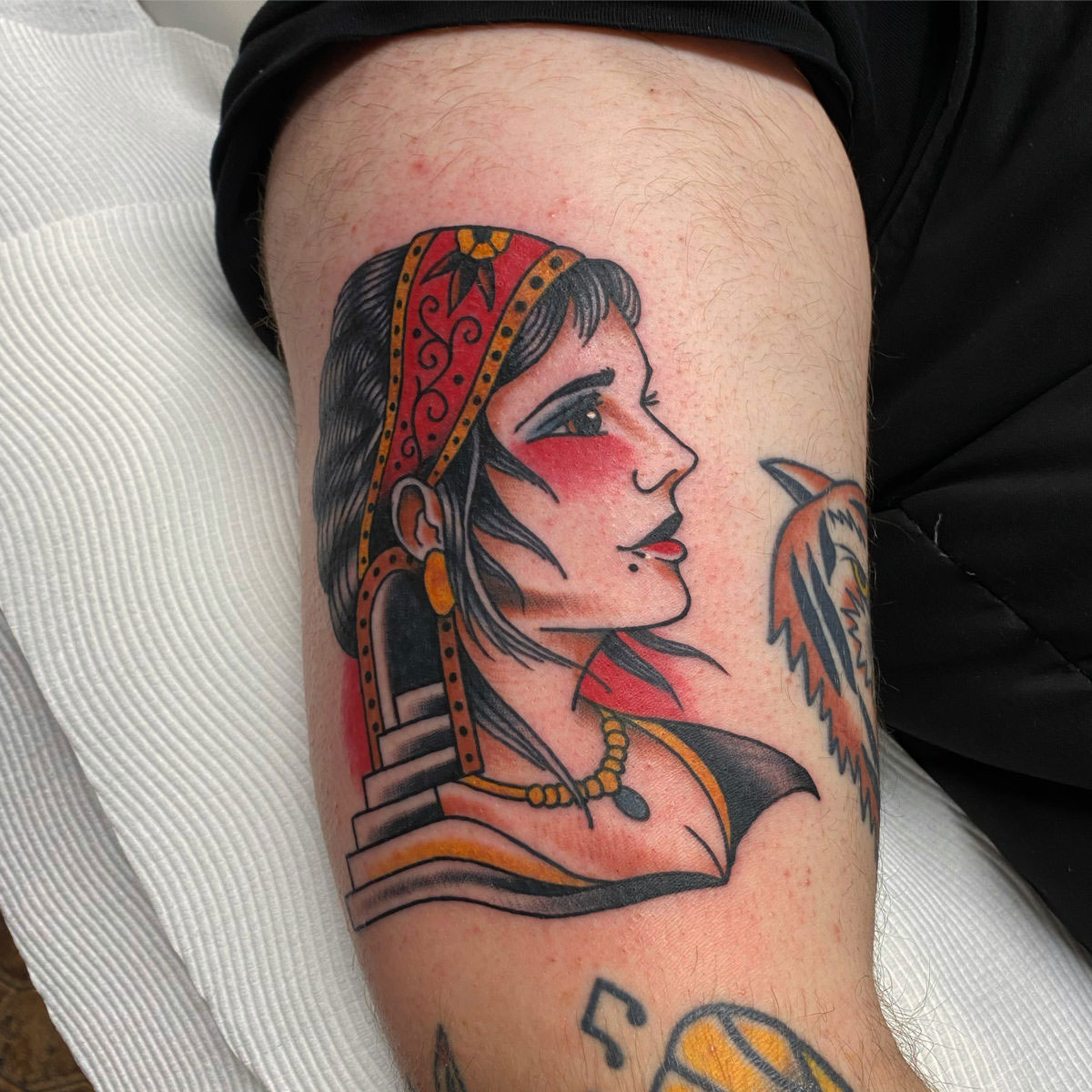 Traditional abstract gypsy lady tattoo with stairs and doorway coming out of her head. tattooed in colour on upper arm.