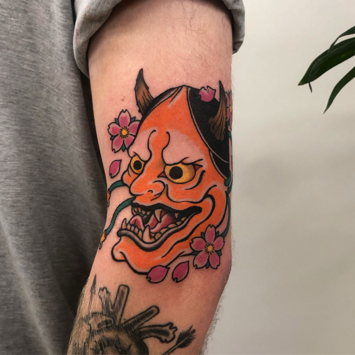 bold bright orange japanese hannya mask with pink cherry blossoms tattooed on upper arm