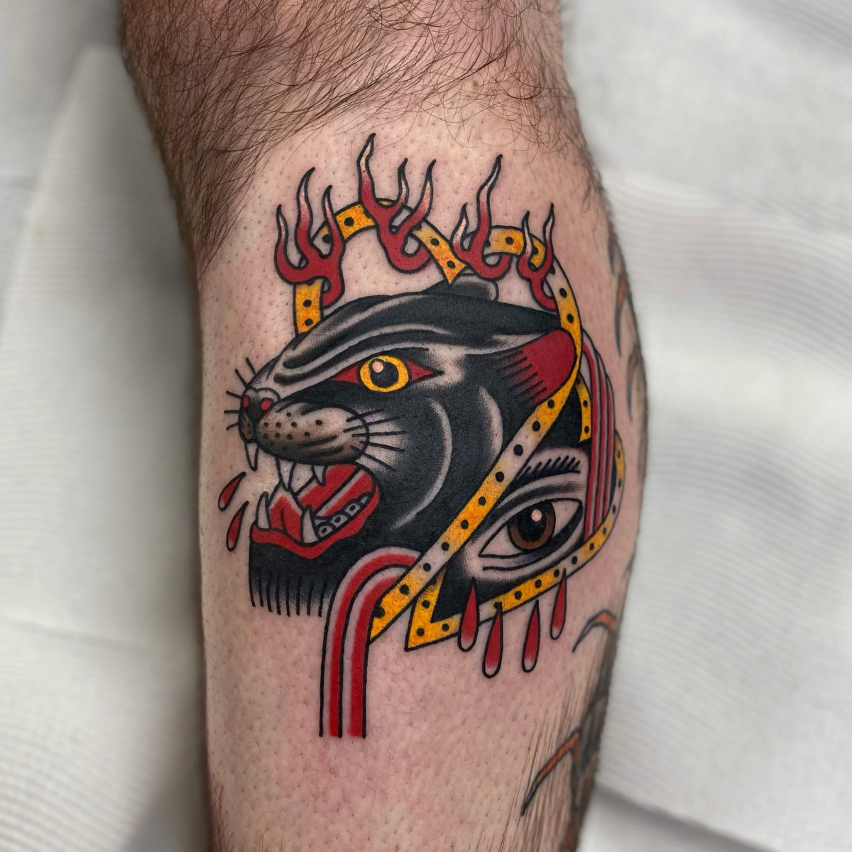 abstract traditional tattoo of panther with gold heart wreath, flames and an eye tattooed on lower leg
