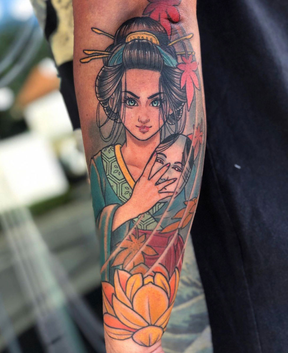 tattoo on forearm with colour showing a geisha holding an onna mask with a lotus and maple leaves