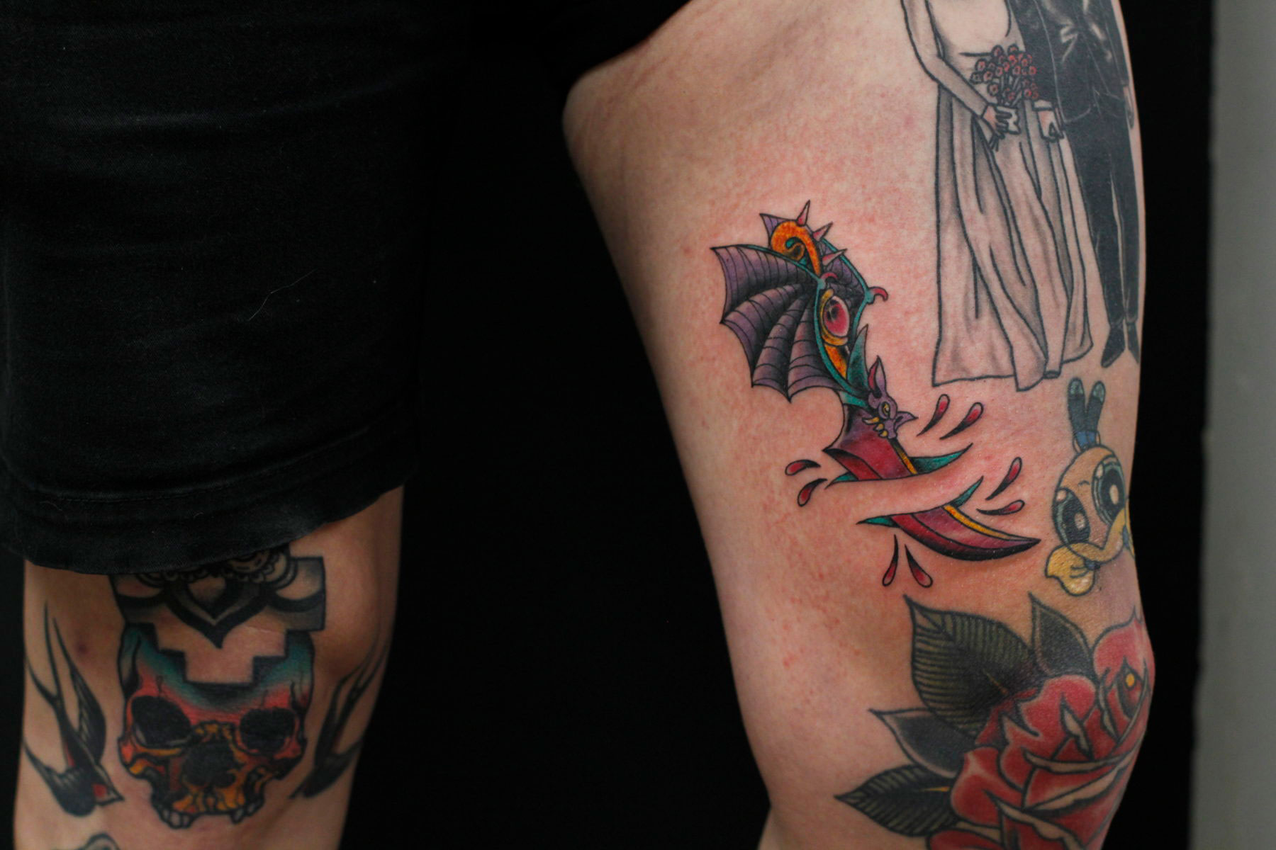 fantasy traditional dagger tattoo with bat wing coming out the back in colour on inner thigh