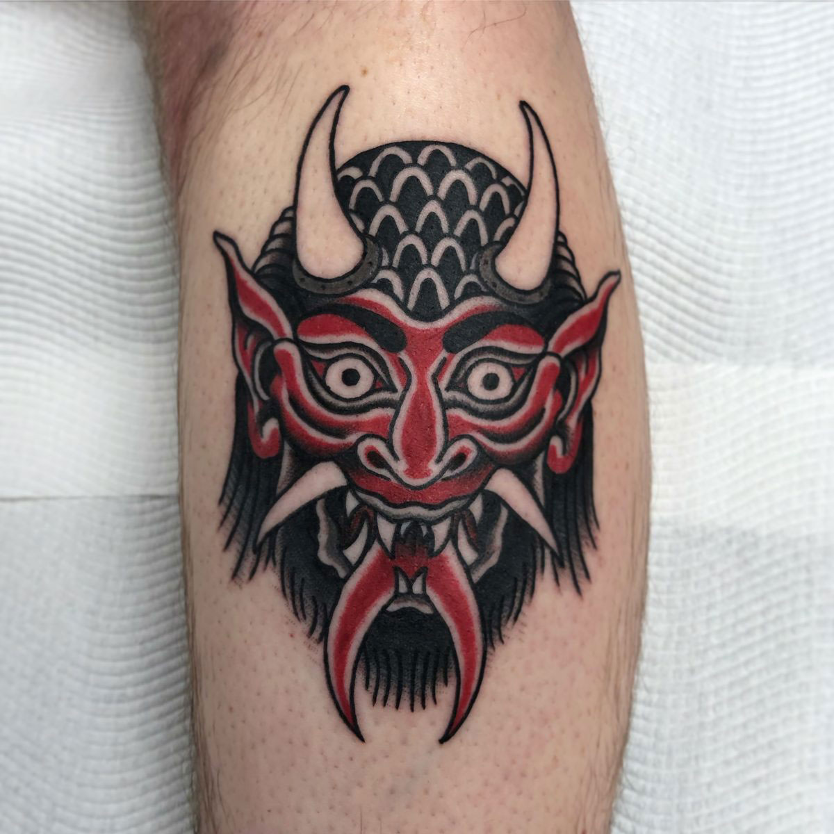 traditional black and red devil head tattooed on calf