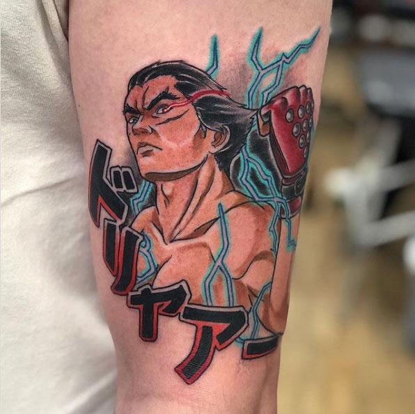 Kazuya from Tekken with Dorya japanese lettering tattooed on the upper arm in colour