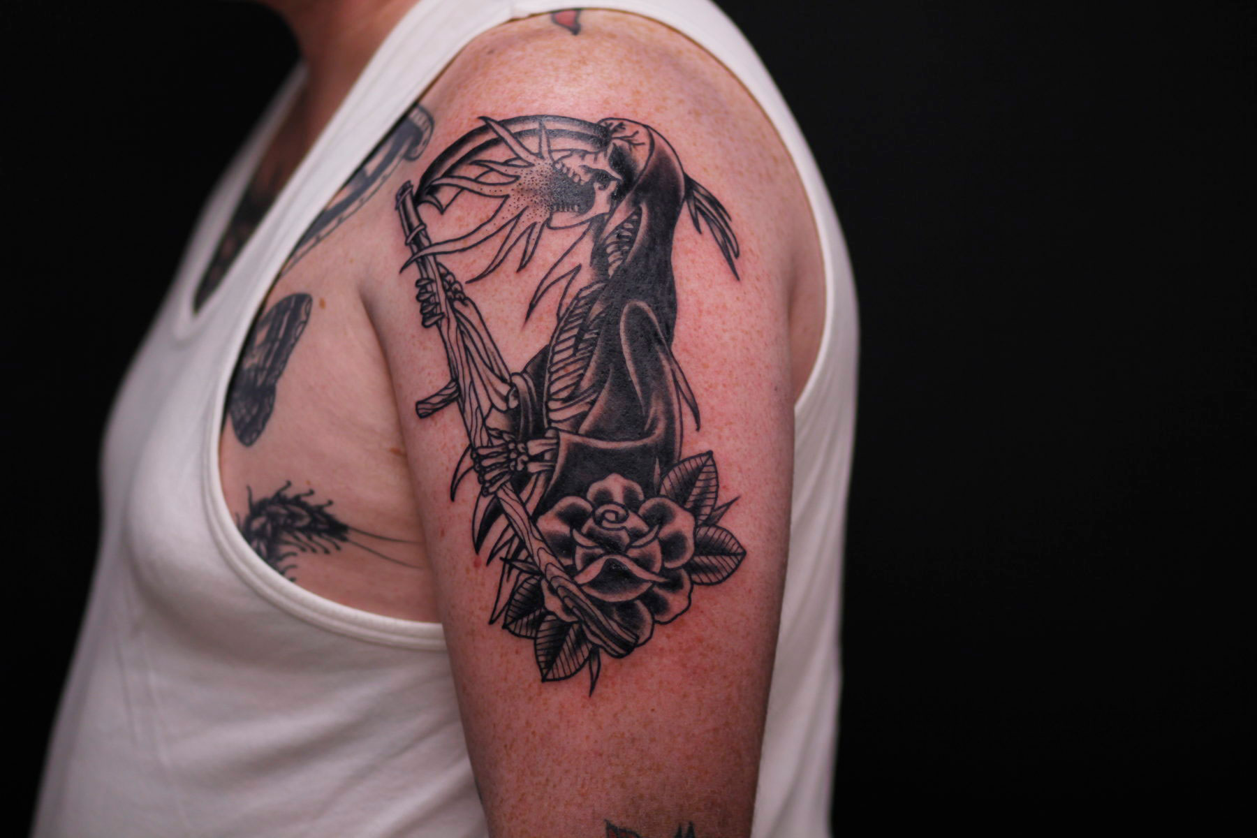 traditional blackwork grim reaper tattoo with his scythe going through his face and flames coming out, traditional rose below