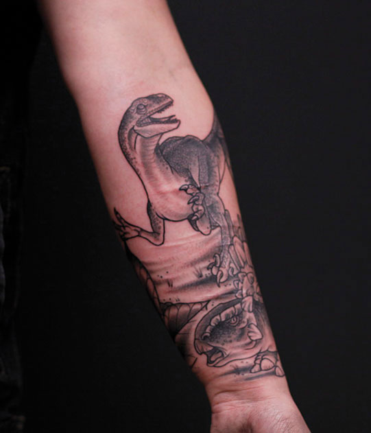 black and grey dinosaur tattoo of a raptor with environmental background around tattooed on forearm